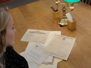 Jessica examines documents containing George Sr.'s promotion to Corporal and his Honorable Discharge forms